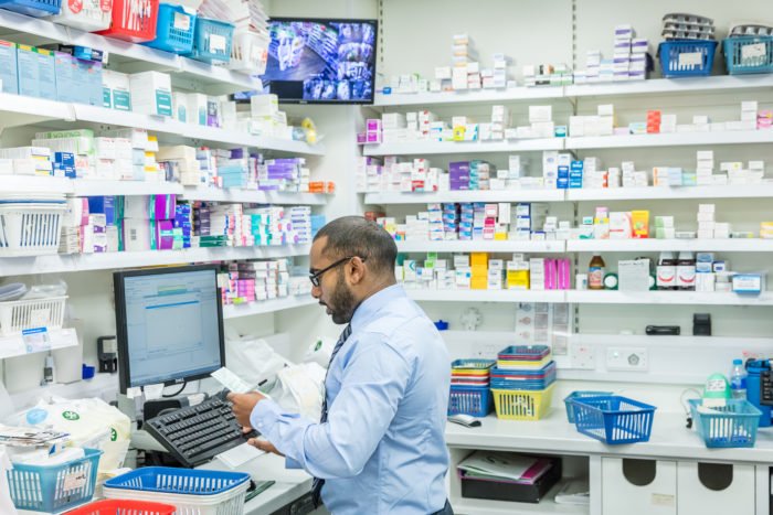 pharmacist at computer with scrip