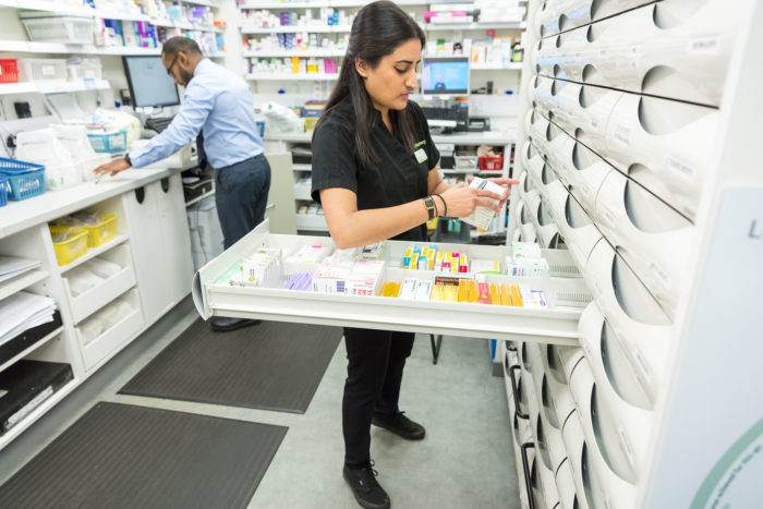 Pharmacy tech at medicines shelves