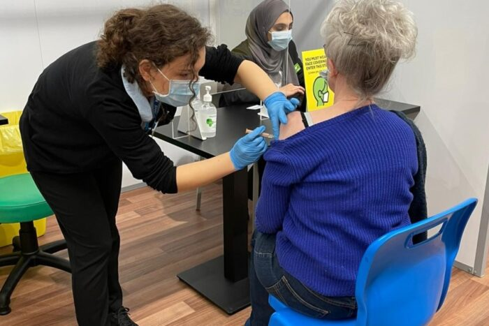 person receives Covid vaccine: all three people re wearing face masks